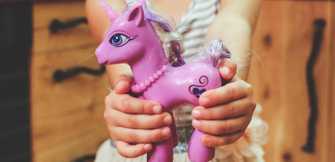 Child holding unicorn toy cropped