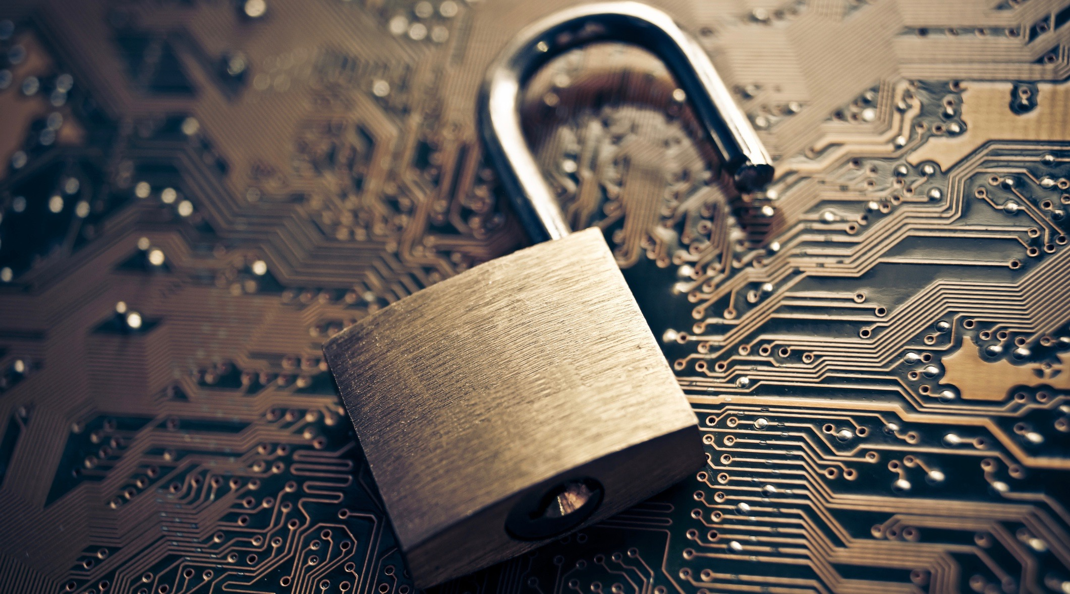 Open padlock on a motherboard signifying security breach