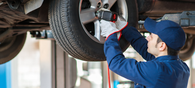 an image of an auto technician repairing a tire