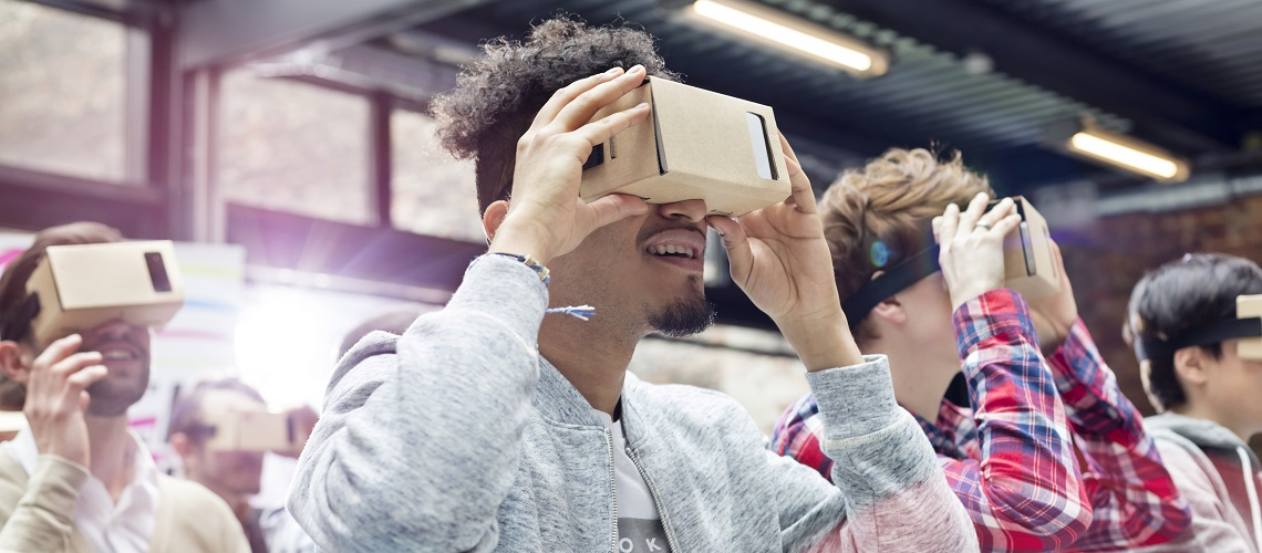 Audience trying virtual reality simulator glasses at technology conference